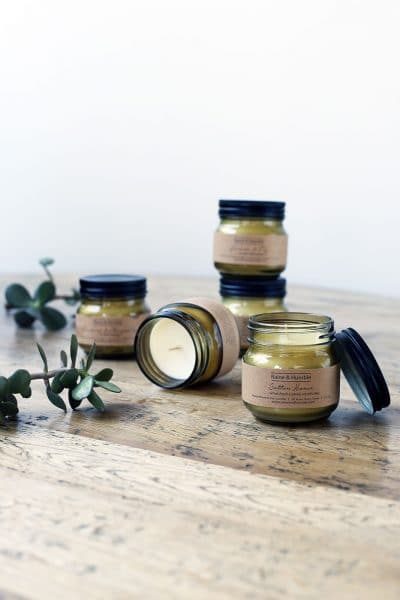 four scented candles in jars presented together on a wooden table