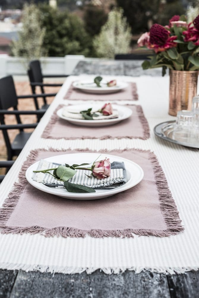 outside-table-set-with-pink-stripe-tablecloth-matching-napkins-and-placemats