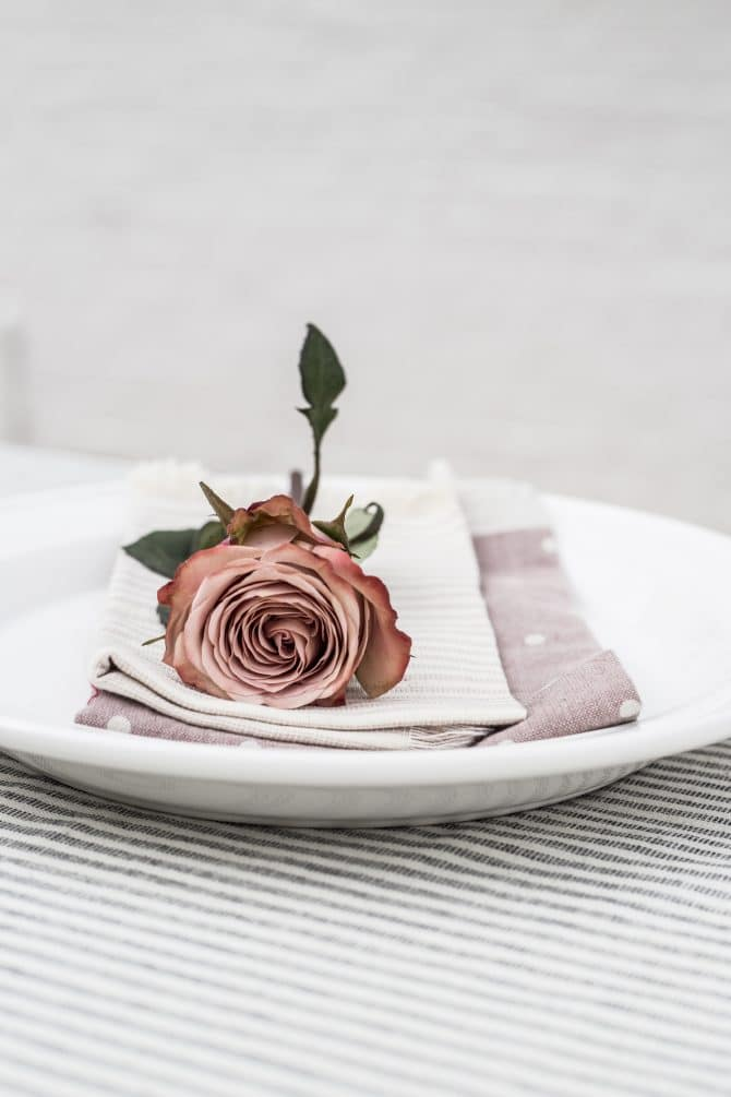 striped-tablecloth-with-plate-napkins-and-rose-display